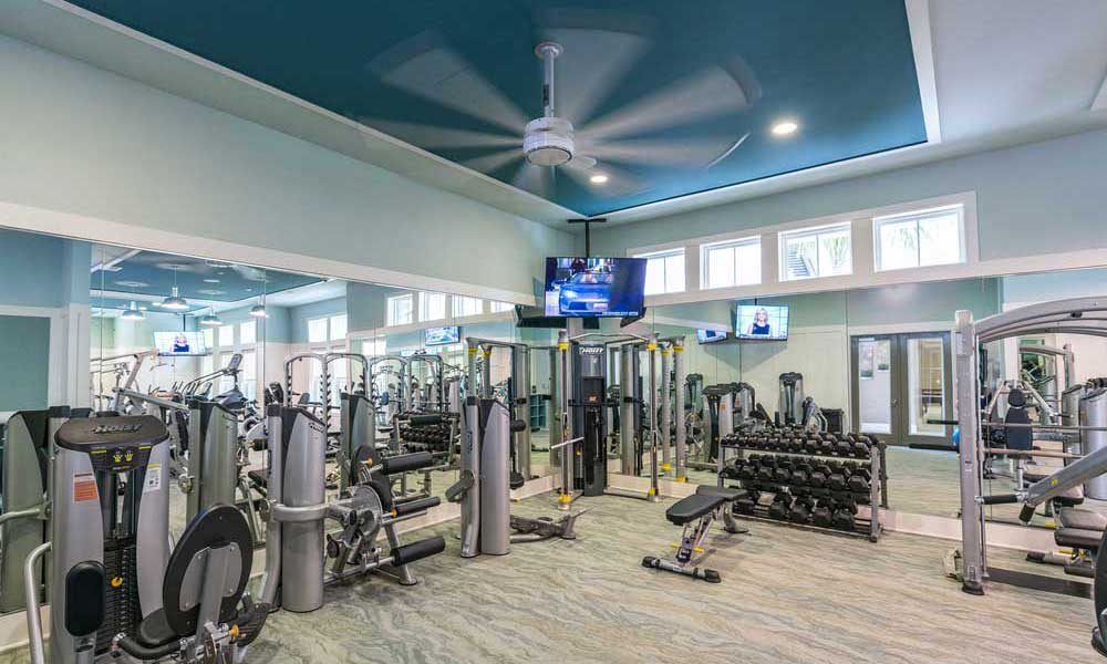 Expansive fitness center with plenty of cardio equipment and exercise machines at Alaqua in Jacksonville, Florida