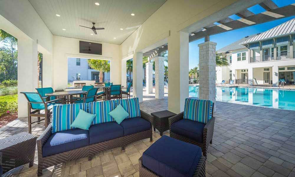 Outdoor lounge area with fans and a flatscreen TV near the pool at Alaqua in Jacksonville, Florida