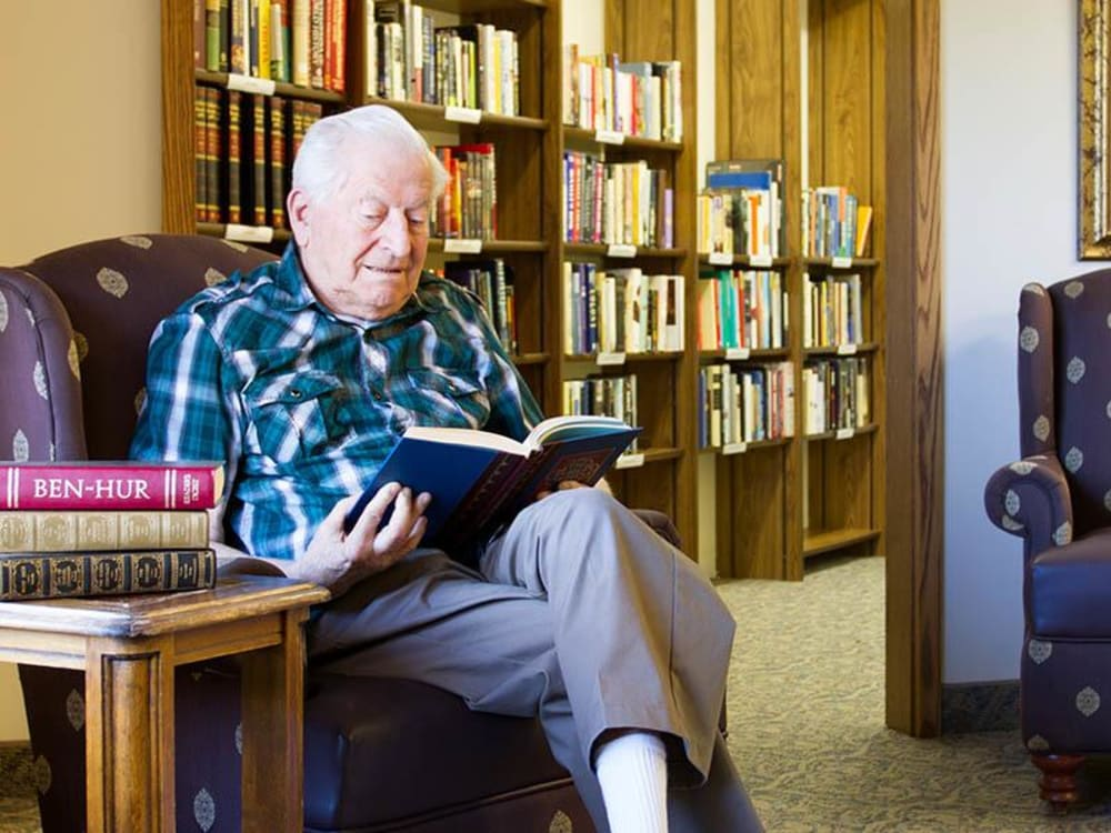 Resident sitting in the library at Royalton Woods in North Royalton, Ohio