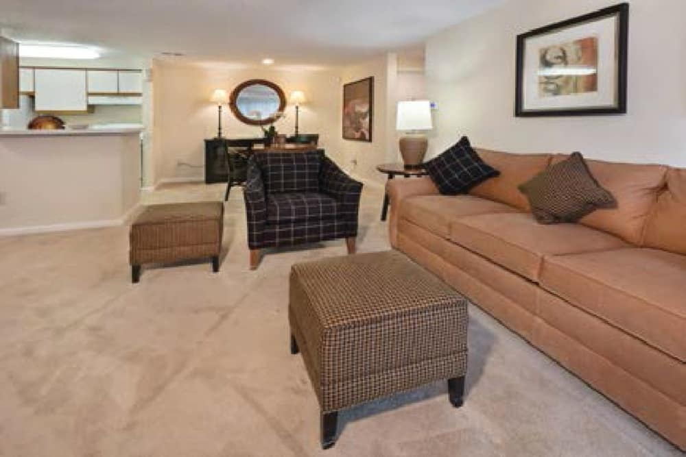 A beige sofa and matching ottomans in a living room at Kingscrest Apartments in Frederick, MD