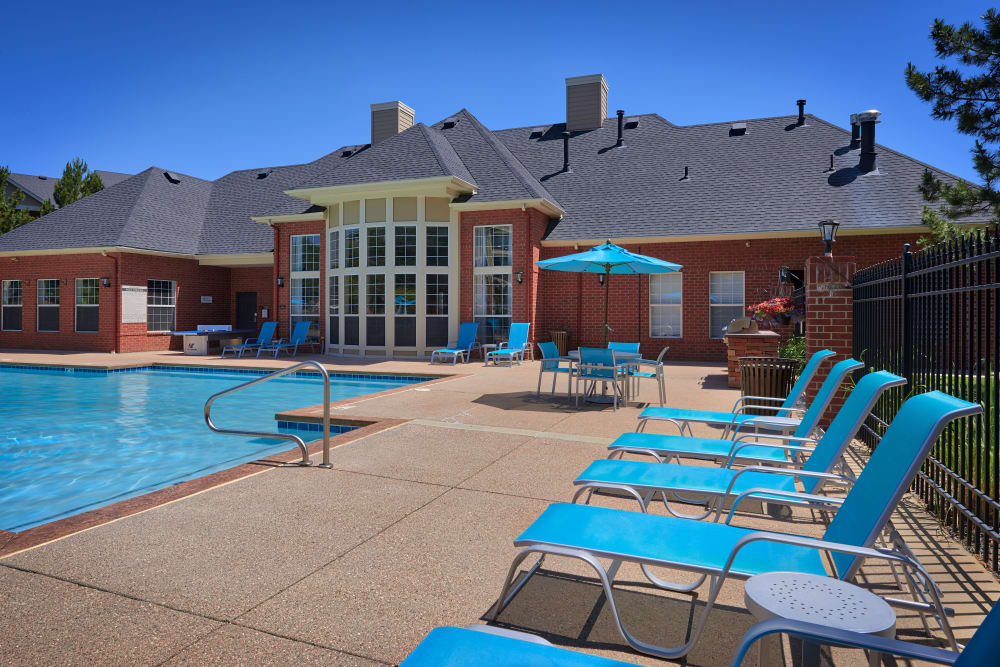 Beautiful resort-style swimming pool with lounge chairs at Skyecrest Apartments in Lakewood, Colorado