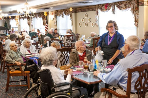 Resident sharing a meal with a friends at The Manor at Market Square in Reading, Pennsylvania
