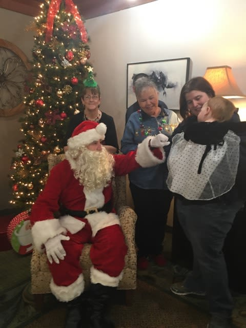 A child visiting Santa at Willow Creek Senior Living in Elizabethtown, KY
