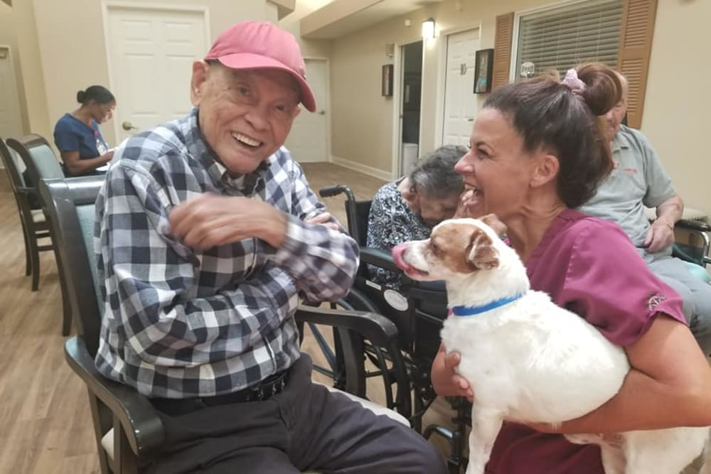 A resident visiting with a dog at Sunlit Gardens in Alta Loma, California