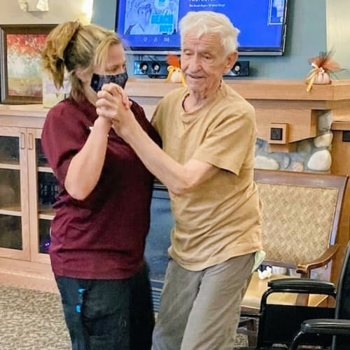 Masked caretaker dancing with a resident at Glen Carr House Memory Care in Derby, Kansas