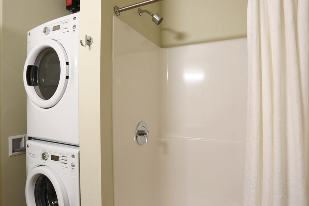 Washer and dryer stacked vertically next to white shower at The Lofts at Glenwood Place in Vancouver, Washington