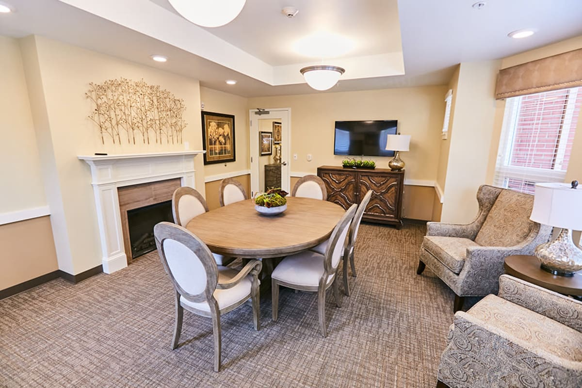 A lounge with a fireplace for residents at Farmington Square Gresham in Gresham, Oregon