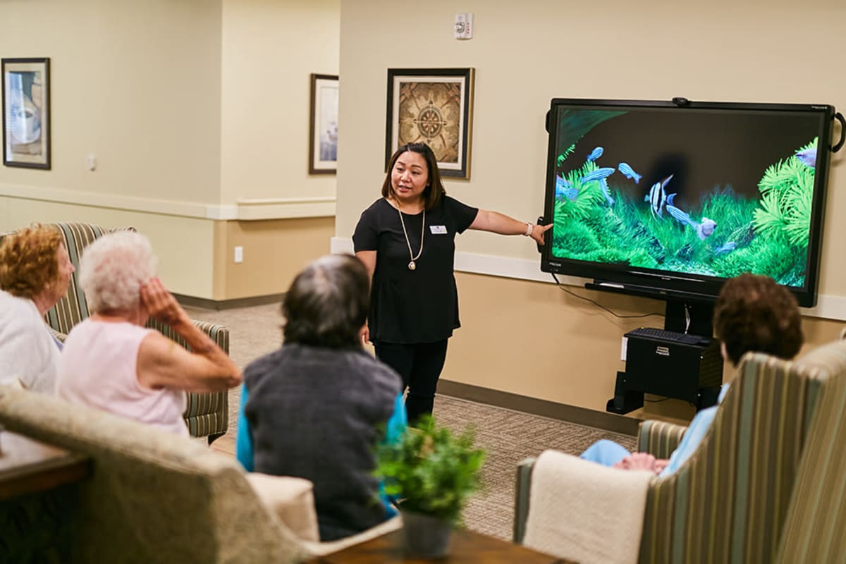 A caregiver having a discussion with residents about fish at Farmington Square Gresham in Gresham, Oregon