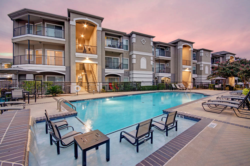 Outdoor community pool with sitting area at Vail Quarters in Dallas, Texas