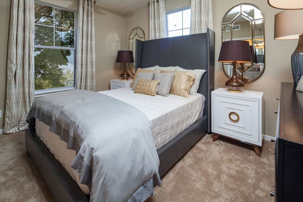 Bed with a table and lamp on both sides at The Spring at Silverton in Fort Worth, Texas