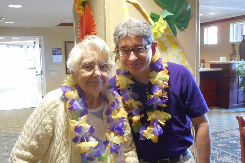 Resident couple enjoying Hawaiian Day at Merrill Gardens at Gilroy in Gilroy, California.
