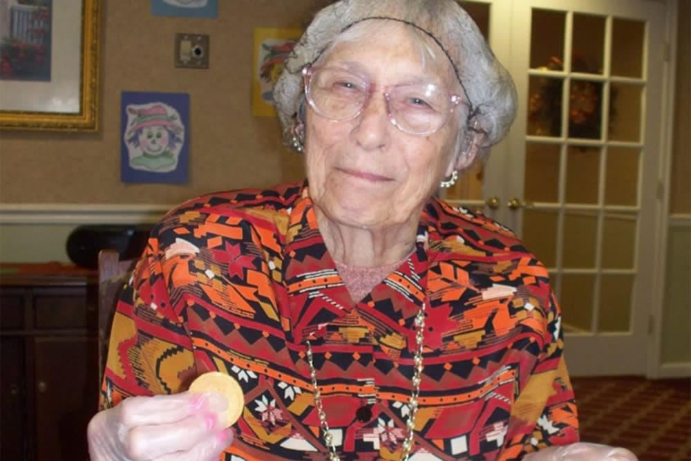 Resident with a bowl and a cracker looking at the camera at Heritage Hill Senior Community in Weatherly, Pennsylvania