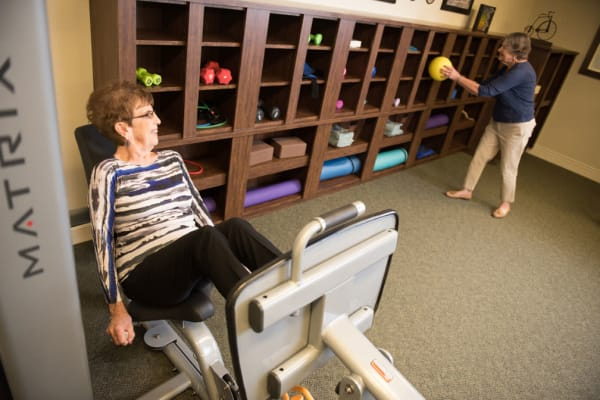 Exercise room with a resident on a leg machine at Deephaven Woods in Deephaven, Minnesota