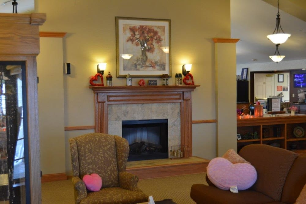 Comfortable chair and sofa near the fireplace at Courtyard Estates at Hawthorne Crossing in Bondurant, Iowa.