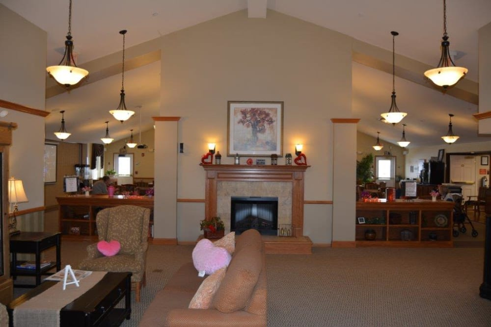 Main entrance lobby with comfortable seating and fireplace at Courtyard Estates at Hawthorne Crossing in Bondurant, Iowa