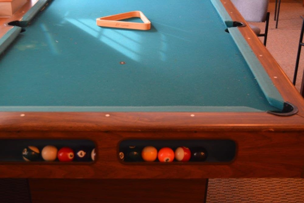 Resident game room with full size pool table at Courtyard Estates at Hawthorne Crossing in Bondurant, Iowa.