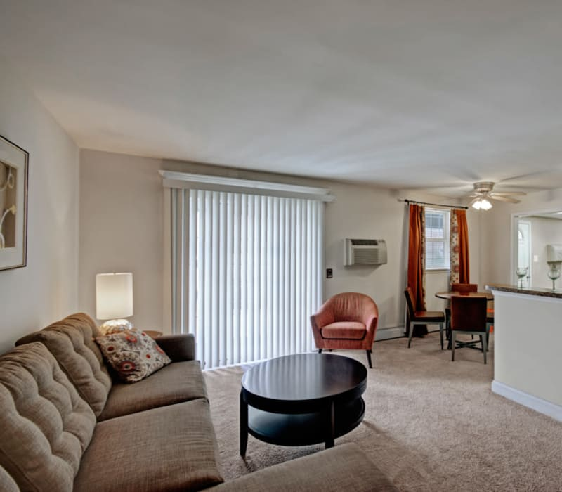 Well-furnished living room area with patio access at Ridley Brook Apartments in Folsom, Pennsylvania