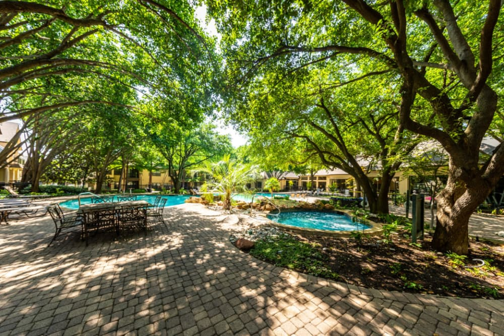 Pool deck area with tables and chairs covered by lush trees at Marquis at Waterview in Richardson, Texas