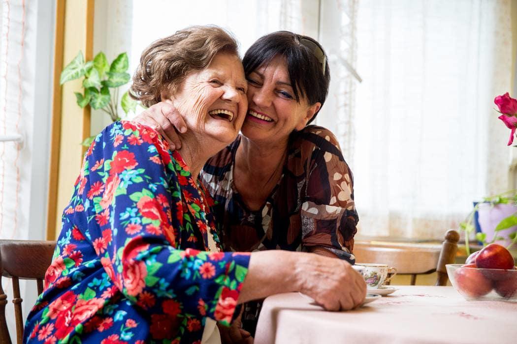 Resident and daughter laughing at Alderbrook Village in Arkansas City, Kansas.
