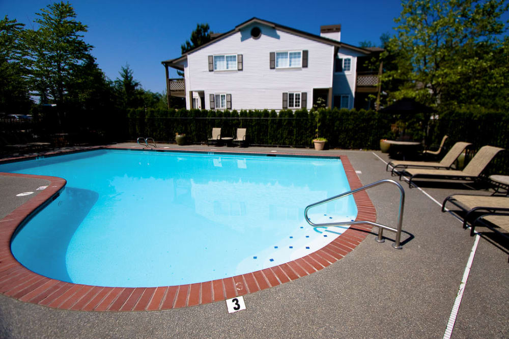 Sparkling pool with sun chairs at Walden Pond Apartments in Everett, Washington