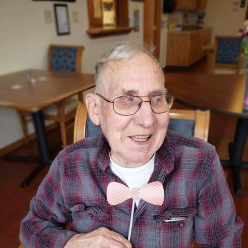 A resident holding a bowtie up to their neck at Alderbrook Village in Arkansas City, Kansas