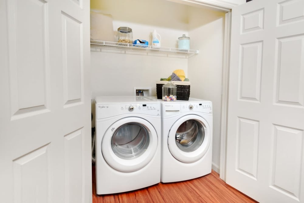 In-home washer and dryer with shelving at The Parc at Greenwood Village in Greenwood Village, Colorado