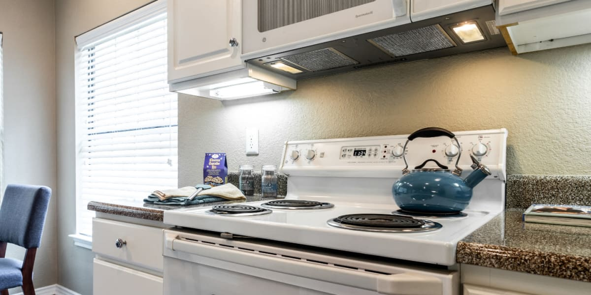 Bright kitchen with laminate counters, white cabinets, and white appliances at Marquis at Waterview in Richardson, Texas