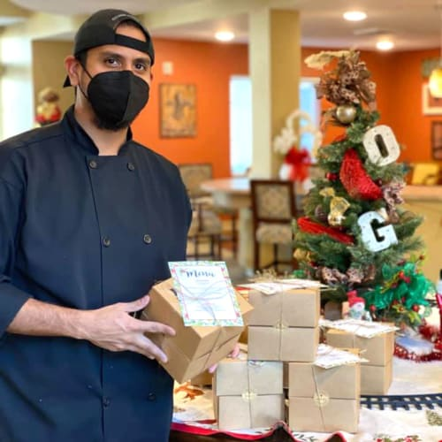 A masked team member setting out presents at The Oxford Grand Assisted Living & Memory Care in McKinney, Texas