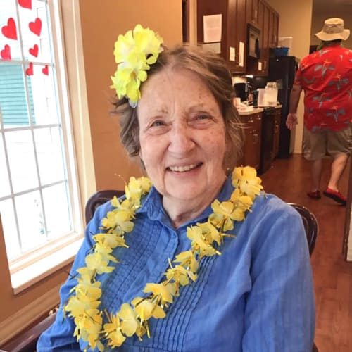 Resident at a party wearing a flower necklace at Oxford Glen Memory Care at Owasso in Owasso, Oklahoma