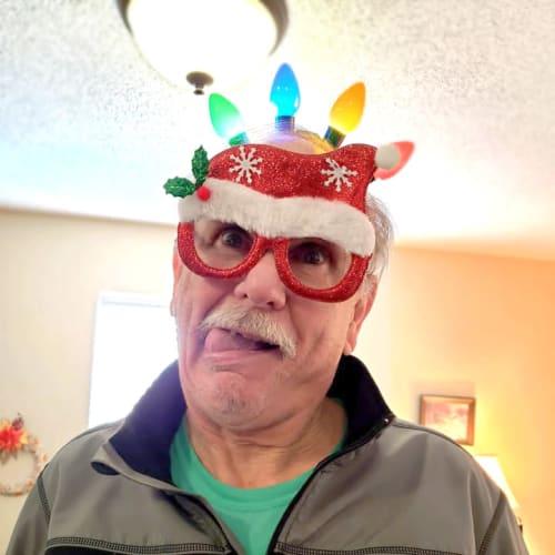 A resident making a goofy face while wearing a light-up cap at Alderbrook Village in Arkansas City, Kansas