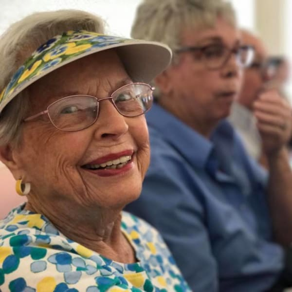 Resident in a sun visor smiling at the camera at Quail Park on Cypress in Visalia, California