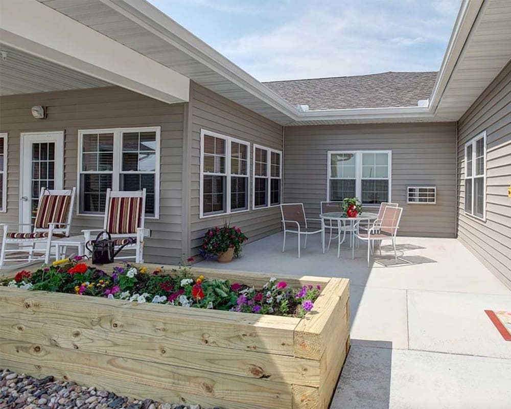 Covered outdoor patio with seating and planter boxes at Milestone Senior Living in Hillsboro, Wisconsin.