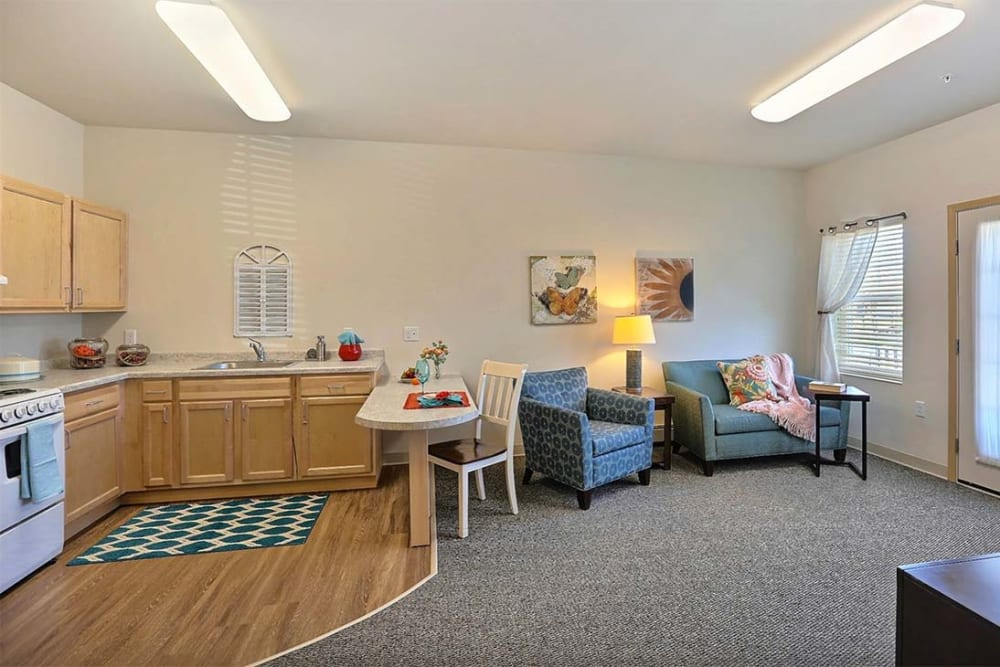 Resident living room with large windows at Milestone Senior Living in Stoughton, Wisconsin.