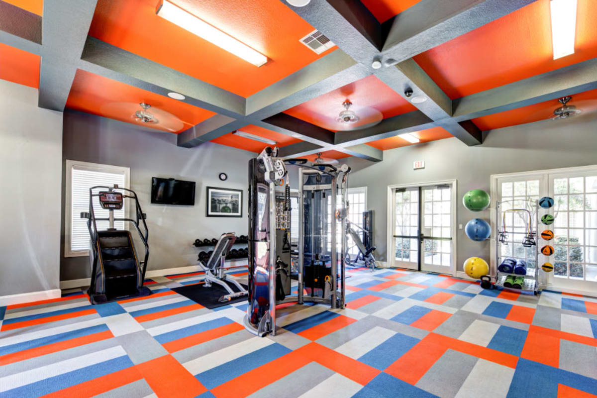 Fitness room with weight machine, stair climber, and medicine balls on rack at Marquis at Silver Oaks in Grapevine, Texas