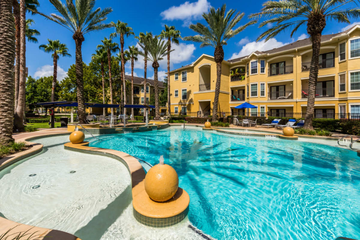 Sparkling resort style pool with water features at Marquis at Clear Lake in Webster, Texas