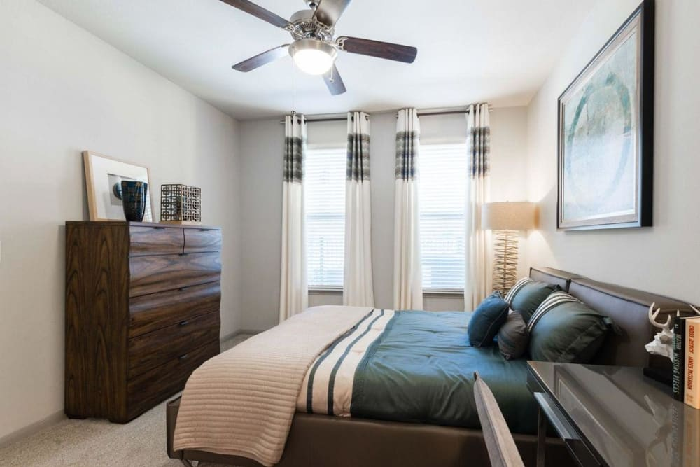 Model bedroom with natural light at Olympus at Waterside Estates in Richmond, Texas