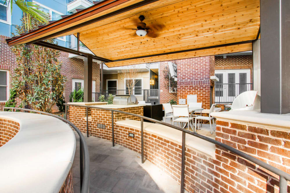 Covered BBQ area with tables, chairs, and cushioned chairs at Marq Midtown 205 in Charlotte, North Carolina