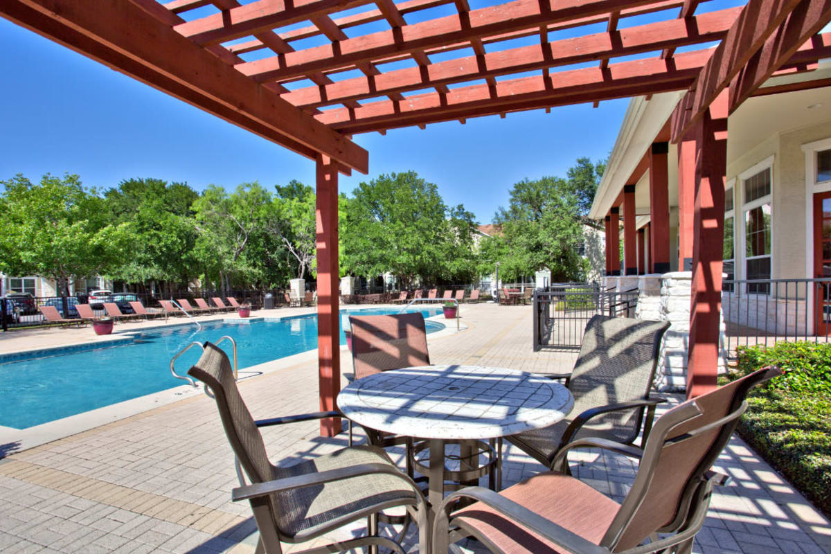 Sparkling swimming pool with poolside lounge area at Marquis Bandera in San Antonio, Texas