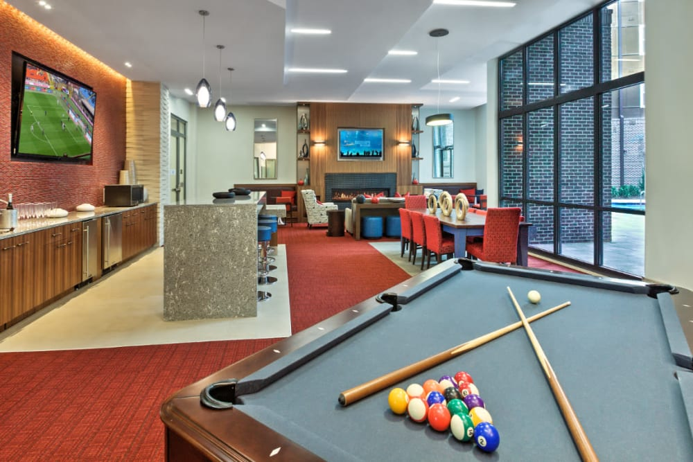 Pool table with community kitchen and dining area in background at Marq Midtown 205 in Charlotte, North Carolina