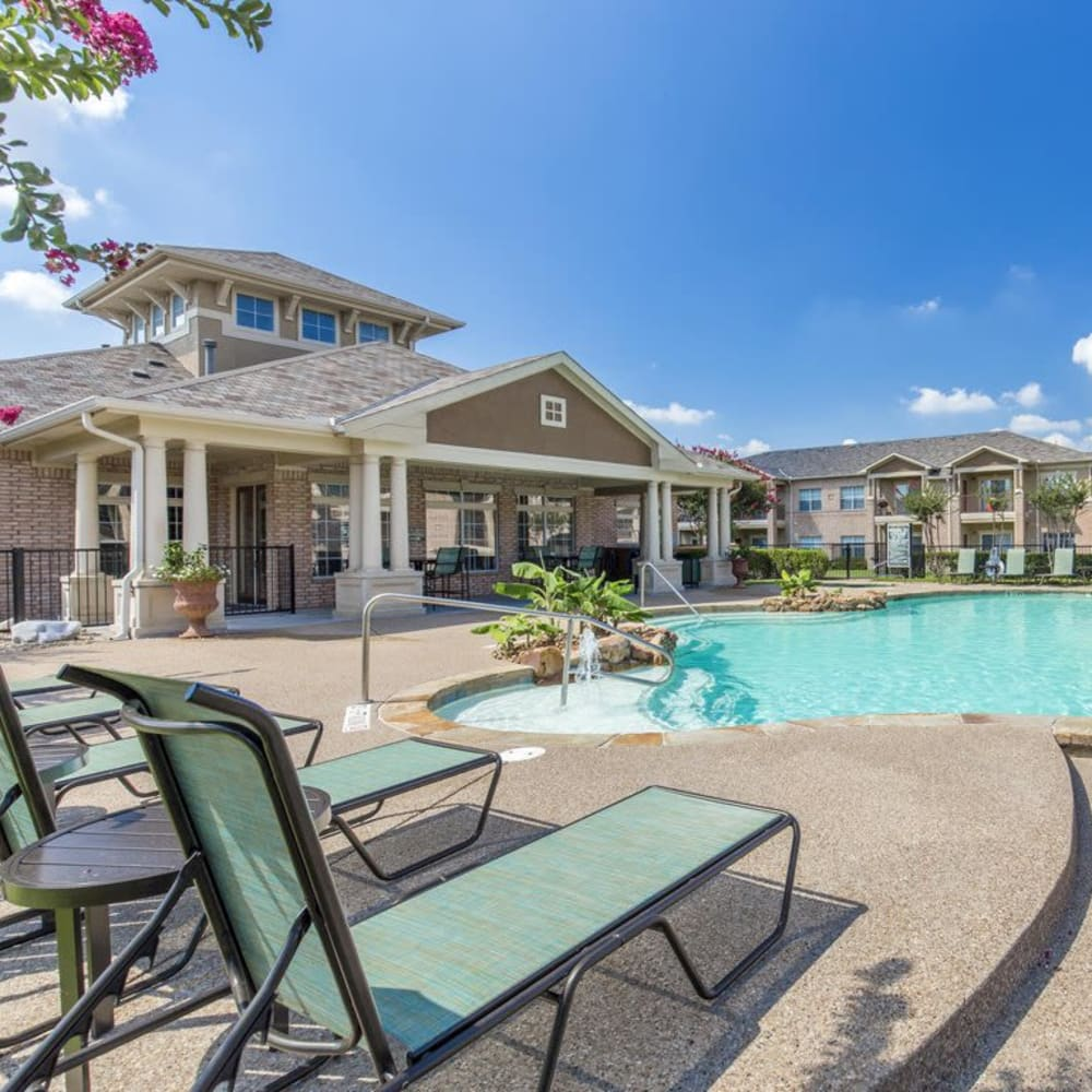 Swimming pool with a sundeck and lounge chairs at Ranch at Hudson Xing in McKinney, Texas