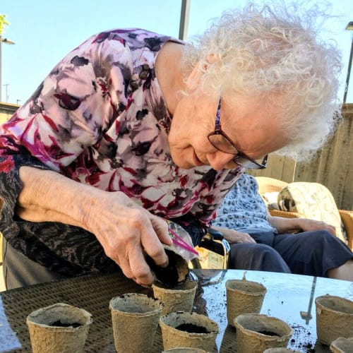 Resident pouring soil into pots at Glen Carr House Memory Care in Derby, Kansas