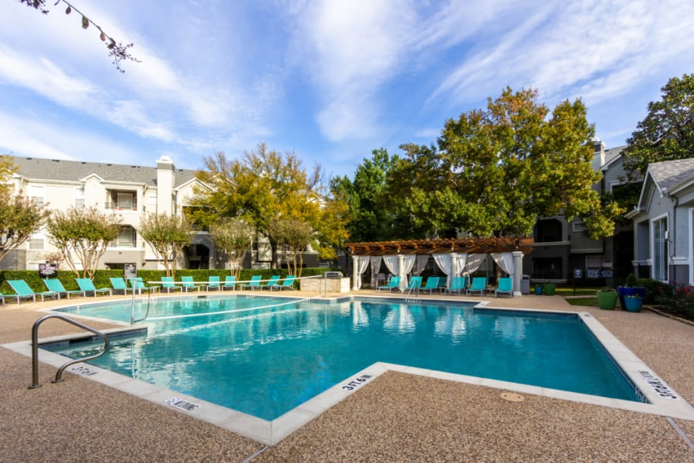 Pool with volleyball net, lounge chairs, and gazebo area at Marquis at Stonegate in Fort Worth, Texas