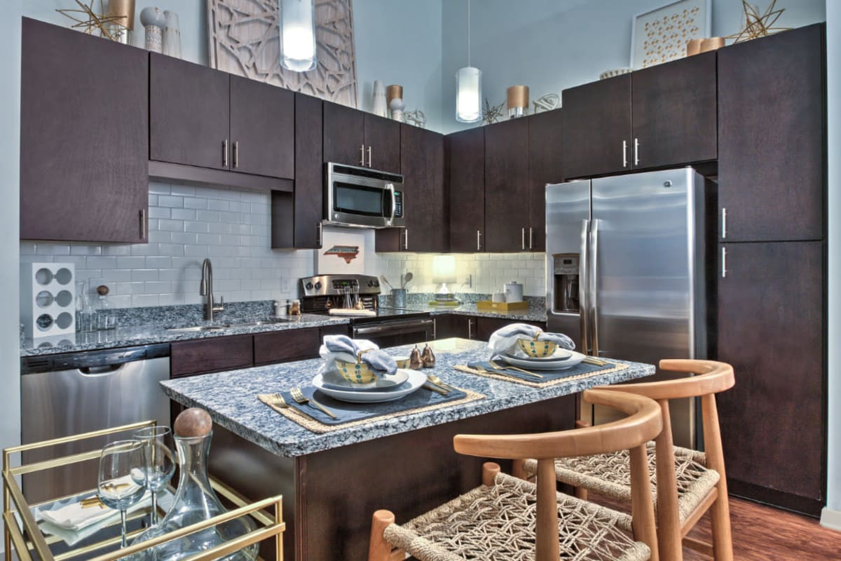 Chic styled kitchen with stainless steel appliances, granite counters, and dark wood cabinets at Marq Midtown 205 in Charlotte, North Carolina