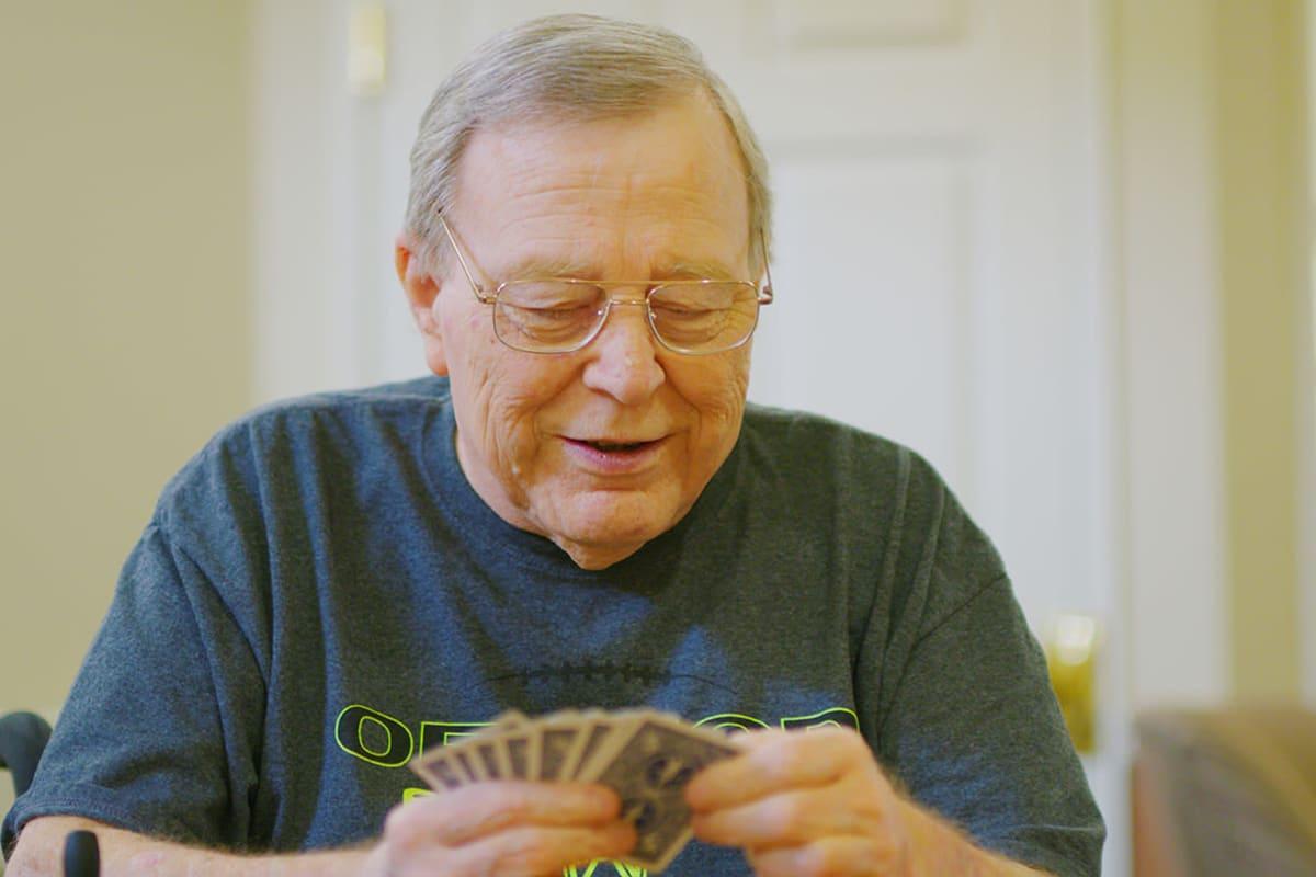 Man enjoying a game of gin rummy at Farmington Square Eugene in Eugene, Oregon