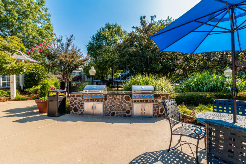 Stone BBQs next to dining tables and chairs with umbrellas at Marquis of Carmel Valley in Charlotte, North Carolina