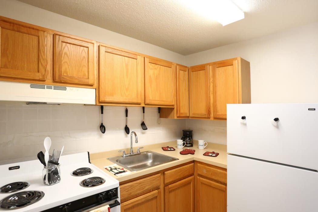 Kitchen sink and cooking range at Bishop - Stratford Court Apartments in Stratford, New Jersey