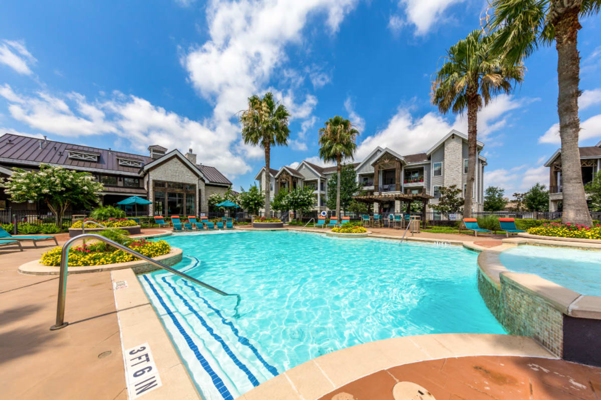 Resort style swimming pool surrounded by lounge chairs at Marquis at Sugar Land in Sugar Land, Texas