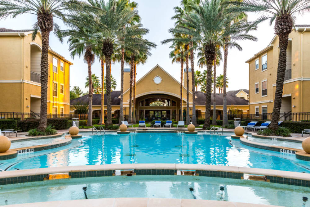 Resort style pool with water features and view of the clubhouse at Marquis at Clear Lake in Webster, Texas
