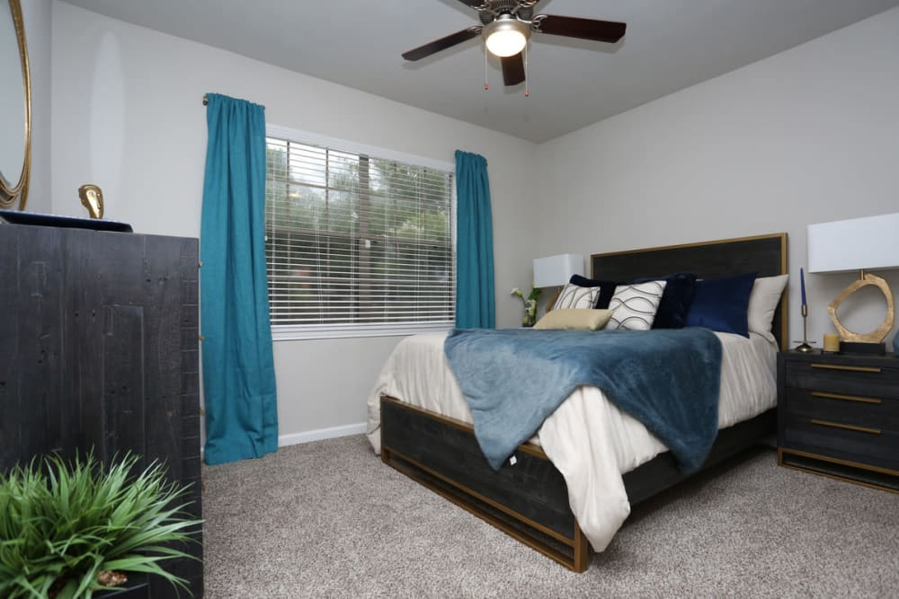 Comfy bed and ceiling fan at Legacy at Cypress in Cypress, Texas