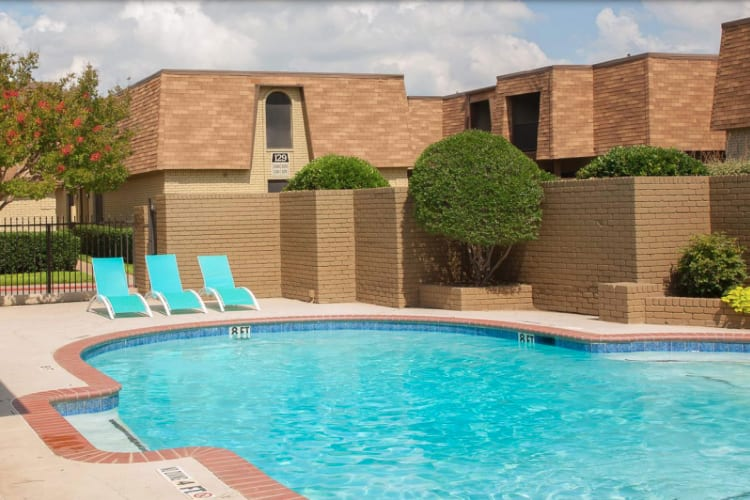 Pool with lounge chairs at The Manchester Apartments in Euless, Texas